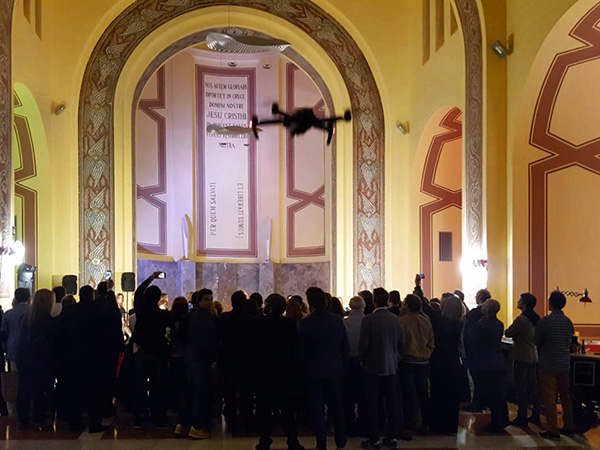 Un dron volant dins de la capella, que està plena de gent, durant una jornada